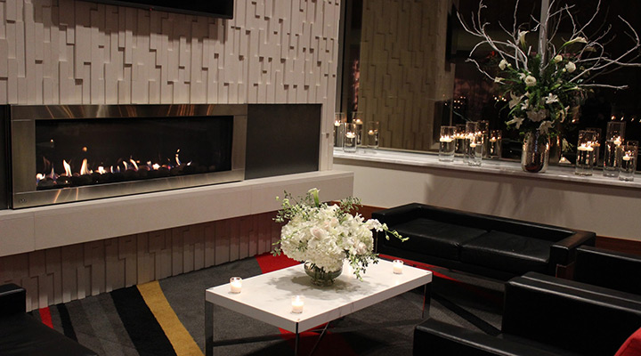 Modern white fireplace with black chairs and white flowers