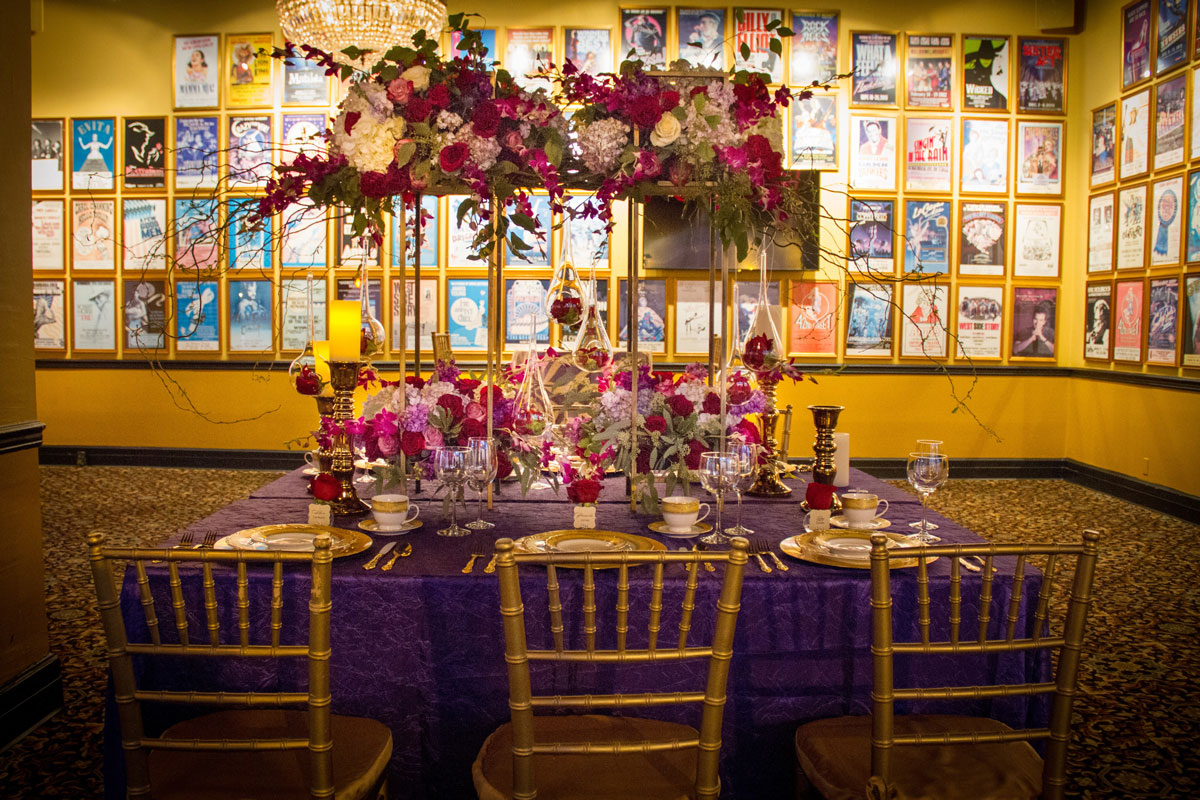 Table settings and centerpieces in front of musical posters
