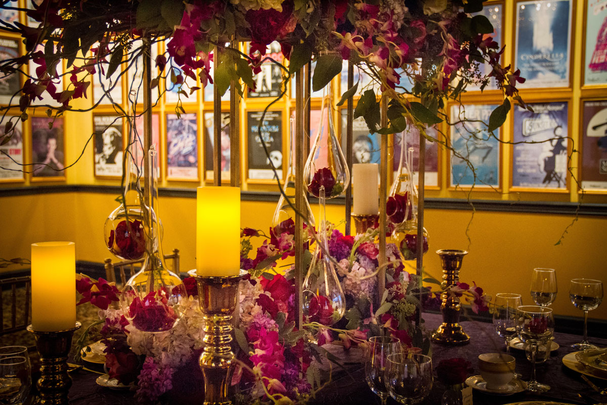 Flower and candle centerpiece in front of musical posters